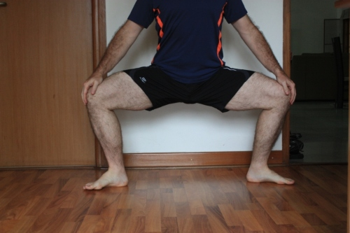 Utkatakonasana (often called goddess pose) variations will show you whether you're getting your knees and toes in line.