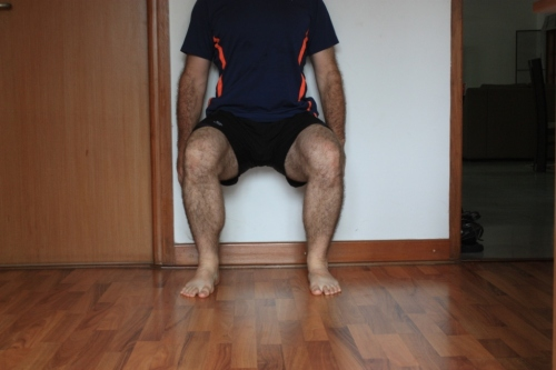 Wall squat: just like sitting on a chair with one's back  to the wall--sans the chair.